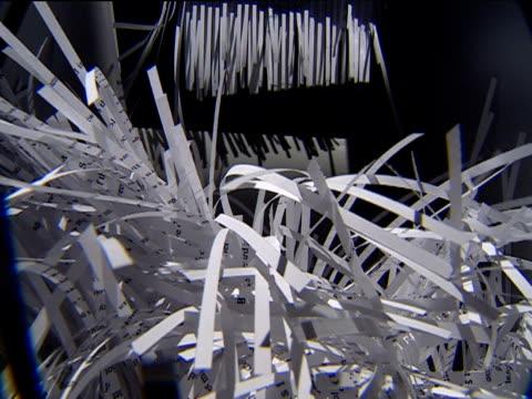paper passes through shredder and falls down burying camera - distruzione video stock e b–roll