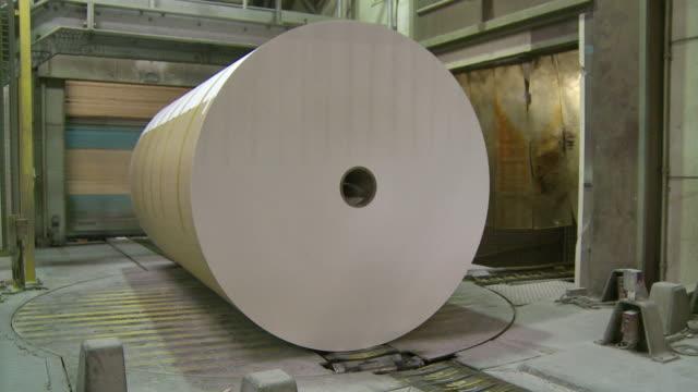 vídeos de stock, filmes e b-roll de ms paper roll passing on conveyor belt in paper mill / glueckstadt, schleswig-holstein, germany - fábrica de papel