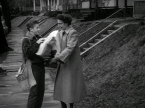 b/w 1950 paperboy helping woman carry grocery bag / they walk up stairs to house / connecticut - carrying stock videos & royalty-free footage