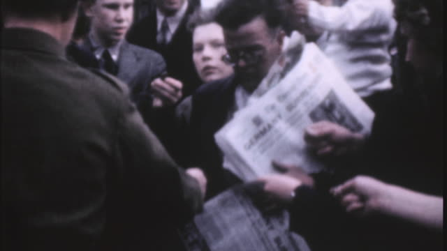 paperboy selling newspapers to the crowd around him and group of soldiers reading the paper on ve day / london, england, united kingdom - 1945 stock-videos und b-roll-filmmaterial