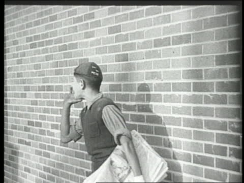 vidéos et rushes de b/w 1924 paperboy standing by brick wall shouting to sell newspapers - 1924