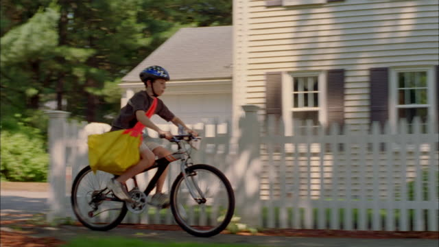 a paperboy throws a paper toward a house. - picket fence stock videos and b-roll footage