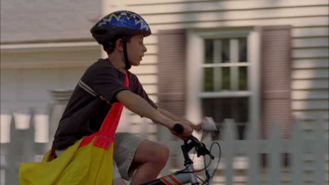 stockvideo's en b-roll-footage met a paperboy throws a paper toward a house. - tuinhek