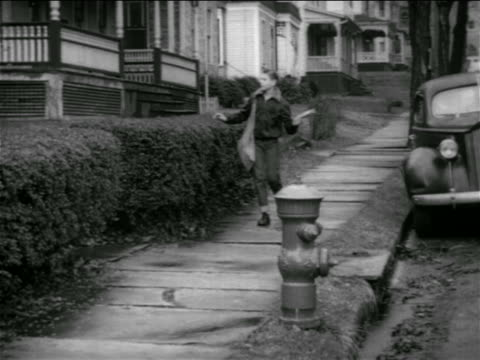 b/w 1950 paperboy walking on suburban sidewalk + throwing newspaper / connecticut / educational - anno 1950 video stock e b–roll