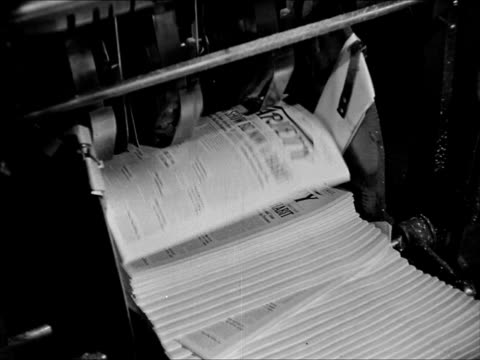 stockvideo's en b-roll-footage met papers coming off press pressmen reading paper folding machine flipping front pages pressman gathering up fold papers male pressmen workers reading... - 1943