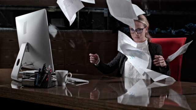 vídeos de stock e filmes b-roll de paperwork falling over businesswoman working late at office desk, super slow motion - papelada