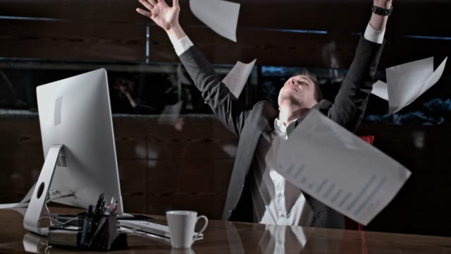vídeos de stock e filmes b-roll de paperwork falling over carefree businessman working late at office desk, super slow motion - papelada