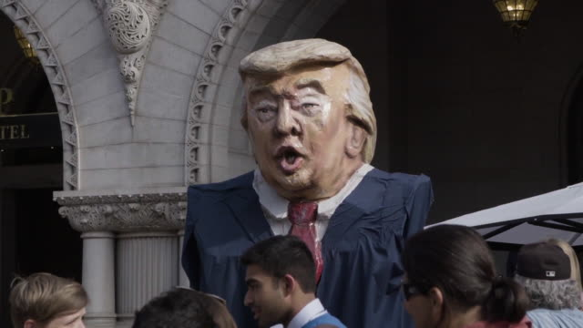 papier mache trump puppet outside of the trump international hotel with protesters - papier stock videos & royalty-free footage