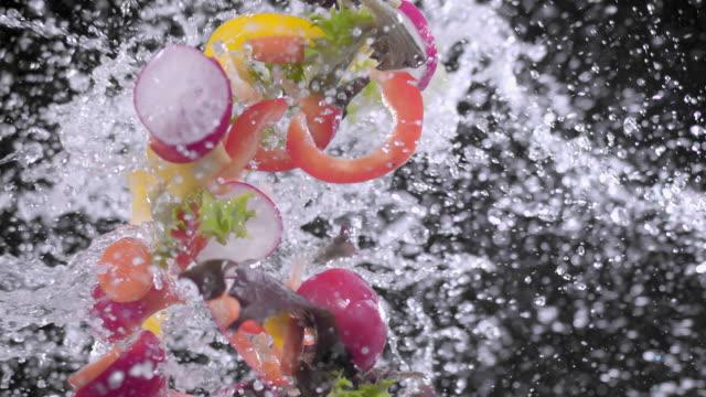 vidéos et rushes de paprika, oignons, radis éclaboussures avec de l'eau super slow motion 1000 fps - radis