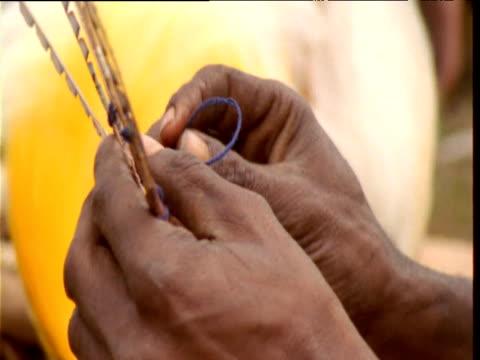 vidéos et rushes de papuan villager stitches bird of paradise feathers into headdress in preparation for mount hagen show, papua new guinea - coiffe traditionnelle
