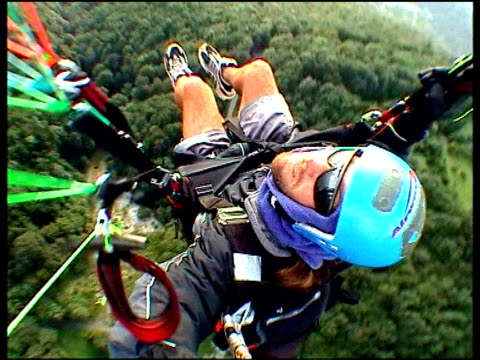 Para glider flying high above forest wearing crash helmet and sunglasses looks up at onboard camera