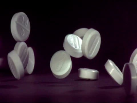 slomo cu paracetamol pills falling on to surface - painkiller stock videos & royalty-free footage