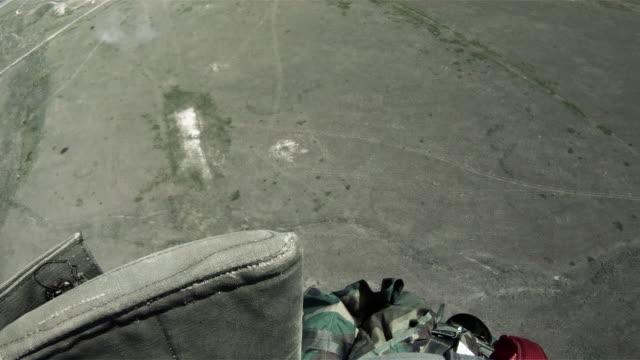 Parachutist in the sky, preparing for landing