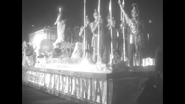 A parade float featuring gladiators and a Greek temple / Jack Benny plays his violin