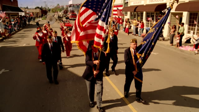 Parade led by war veterans and followed by high school marching band, child beauty queen in red sports car, and horse-drawn carriage proceeding down street with spectators waving from sidelines / California