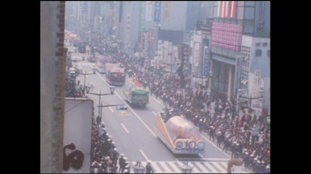 a parade maneuvers along ginza street in honor of the meiji 100 year anniversary grand ginza festival in japan. - 1960~1969年点の映像素材/bロール