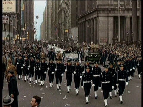 vídeos de stock e filmes b-roll de parade moves down the street in new york city / cars are followed by people marching / confetti falls from the sky / a soldier waves his hat while... - enfeites para a cabeça