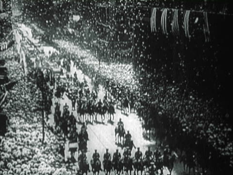 parade moving through the streets of new york / police holding back the crowd / ticker tape falling down in the street - 1927年点の映像素材/bロール
