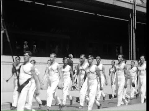 1935 b/w montage parade of gymnasts during international gymnasts gathering / zurich, switzerland - marschieren stock-videos und b-roll-filmmaterial