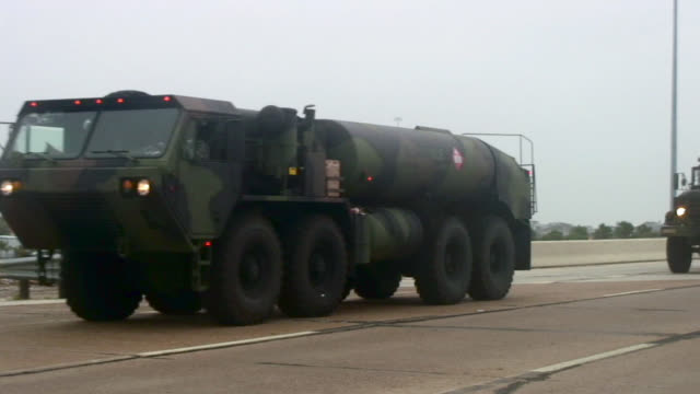 Parade of military vehicles driving into hurricane disaster zone.