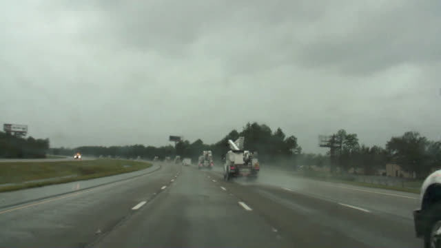 parade of utility trucks driving into hurricane disaster zone. - evacuazione video stock e b–roll