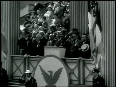 vídeos y material grabado en eventos de stock de parade, officials in reviewing stand w/ nra eagle symbol below. people walking in parade w/ many people standing. nra sign & cleveland's honor roll... - 1933