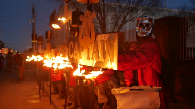 parade participants hold flambeaux torches at the beginning of the orpheus parade in new orleans during mardi gras the traditional torches contain... - gras stock videos and b-roll footage