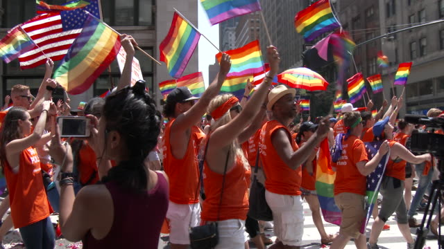 Parade participants holding rainbow flags come out in record numbers and march in solidarity on 5th Avenue during the Gay Pride Parade in NYC