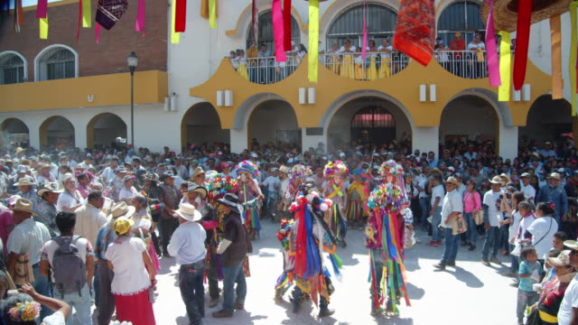 parade participants in bright-colored costumes at zoque coiteco carnival in chiapas village. mexican syncretism tradition. high angle view establishing shot - mexikanischer abstammung stock-videos und b-roll-filmmaterial