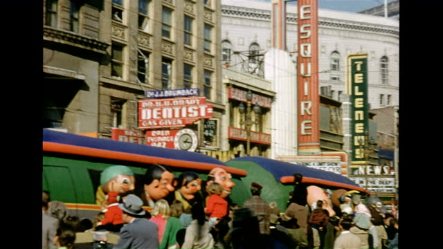 vidéos et rushes de / parade with balloons and floats / train with animal heads at the windows and inflatable people passes by crowd of sightseers / snake and dog float... - char de défilé
