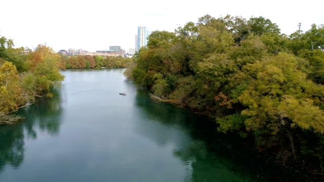 vídeos de stock e filmes b-roll de paradise barton creek flying out into town lake then austin , texas skyline view - town
