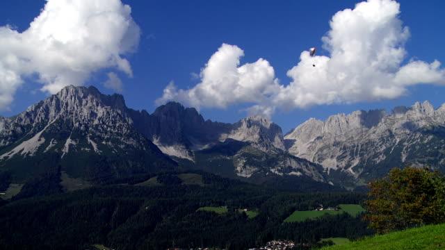 vídeos y material grabado en eventos de stock de crucero frente a las montañas alpinas de parapente - tirol