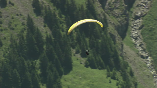 aerial ts zo paraglider flying above mountains, engleberg, bern, switzerland - alpi video stock e b–roll