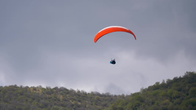 paraglider flying over mountains in cloudy day - lightweight stock videos & royalty-free footage