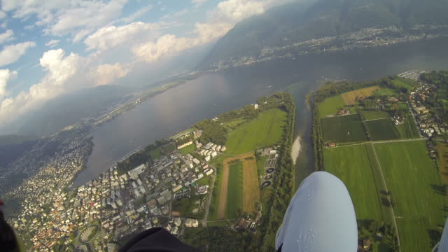 POV paraglider flying over river next to town