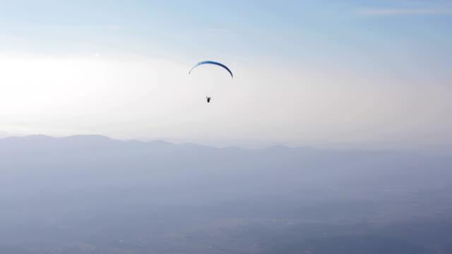 vídeos de stock, filmes e b-roll de parapente, planando acima de um vale ao entardecer - paraquedismo
