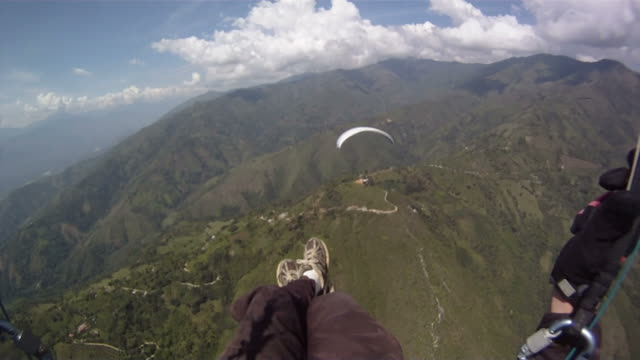 Paraglider In Air Folowing Behind Another Paraglider