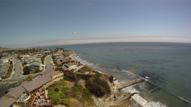 paraglider sails past and waves midair - hang gliding stock videos and b-roll footage