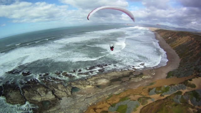 a para-glider soars above crashing waves in the sea. - paragliding stock videos & royalty-free footage