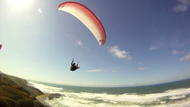 a para-glider soars by crashing waves in the sea. - paragliding stock videos & royalty-free footage