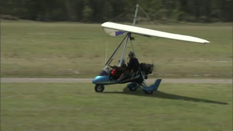 vídeos y material grabado en eventos de stock de a paraglider takes off from a grassy field. - motor eléctrico