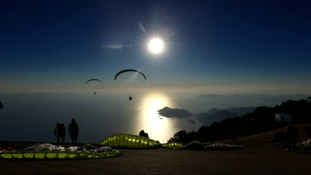 Paragliders are seen over the mountains at sunset after taking off from Baba Mountain on September 5 2017 in Oludeniz Turkey Turkey's tourism...