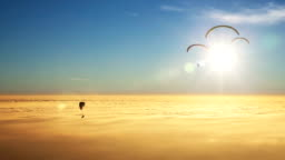 Paragliders on a sea of golden clouds with sun