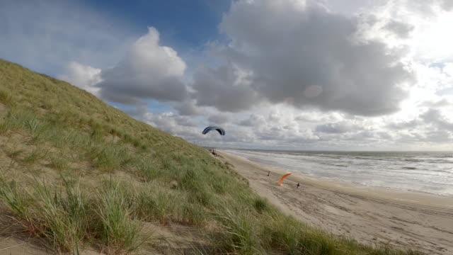 vidéos et rushes de paragliders soaring in netherlands beach - parapente