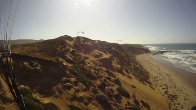 paragliding, first-person view of coasting above beach dunes - パラグライディング点の映像素材/bロール