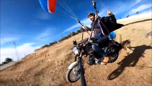 paragliding pilot hasan kaval flew over the white travertines of pamukkale in southwestern turkey with the motorcycle hanging on his parachute.... - game show bildbanksvideor och videomaterial från bakom kulisserna