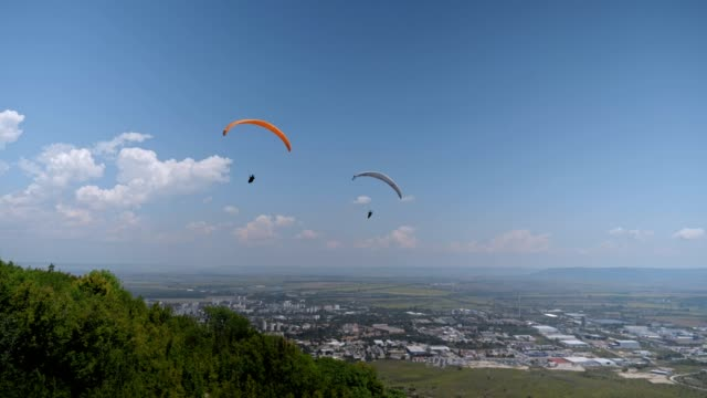 ws pan pov paragliding pilot in the mid-air, flying over a city, urban skyline, cross country pilot, extreme sports, adventure - wide stock videos and b-roll footage