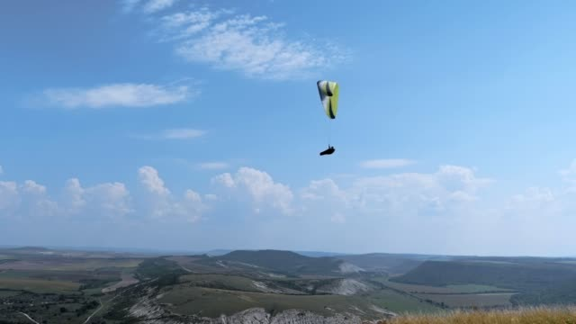 WS PAN POV Paragliding pilot in the mid-air, flying over a city, urban skyline, cross country pilot, extreme sports, adventure