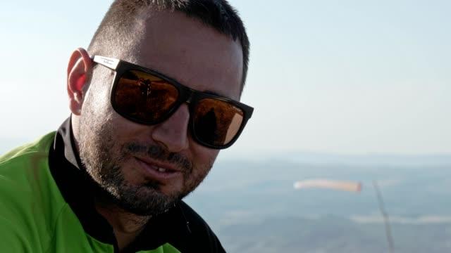 vidéos et rushes de cu pilote de parapente parlant de vol, pilote de cross-country, sports extrêmes, aventure - extreme close up