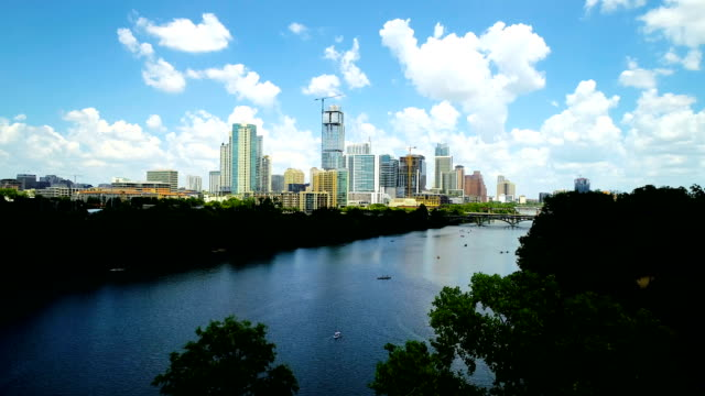 paraide in austin texas puffy white clouds and blue waters of lady bird lake - austin white stock videos & royalty-free footage